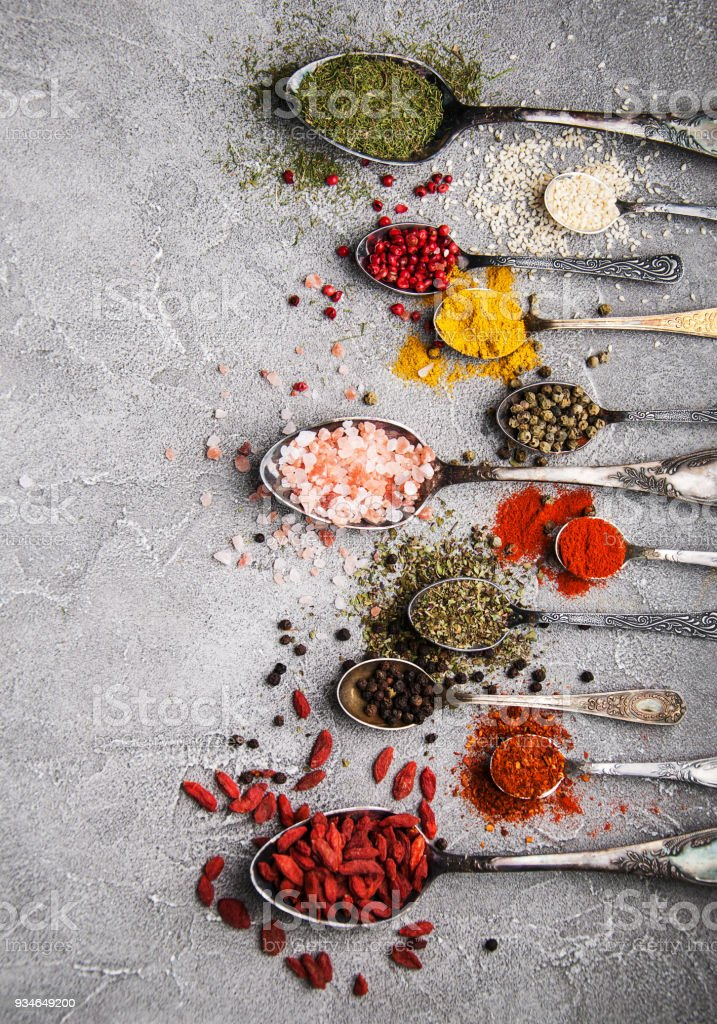 Different kind of spices in vintage spoons stock photo