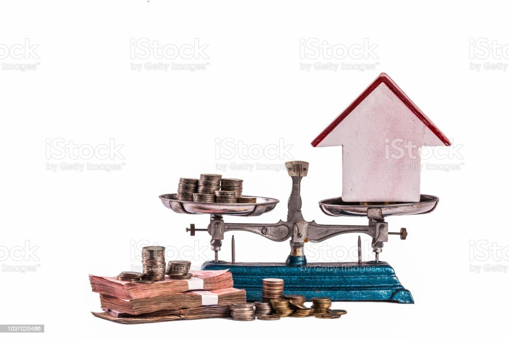Different kinds money scale with model home stock photo