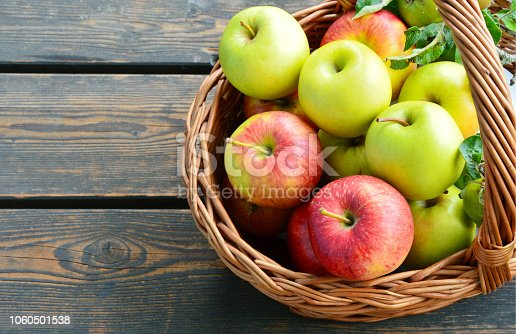 3 Different kinds of apples and the tasty benefits of each. colorful and various kinds of apples in the basket on wooden background.