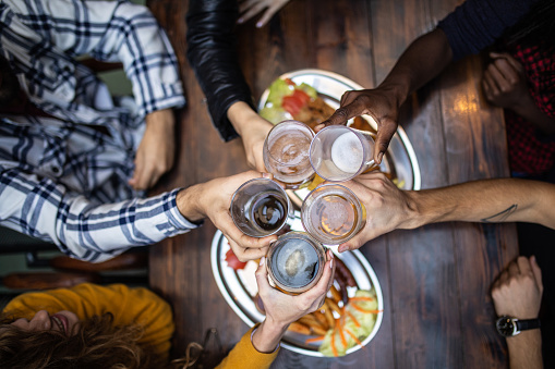 High view on five friends having celebratory toast at restaurant