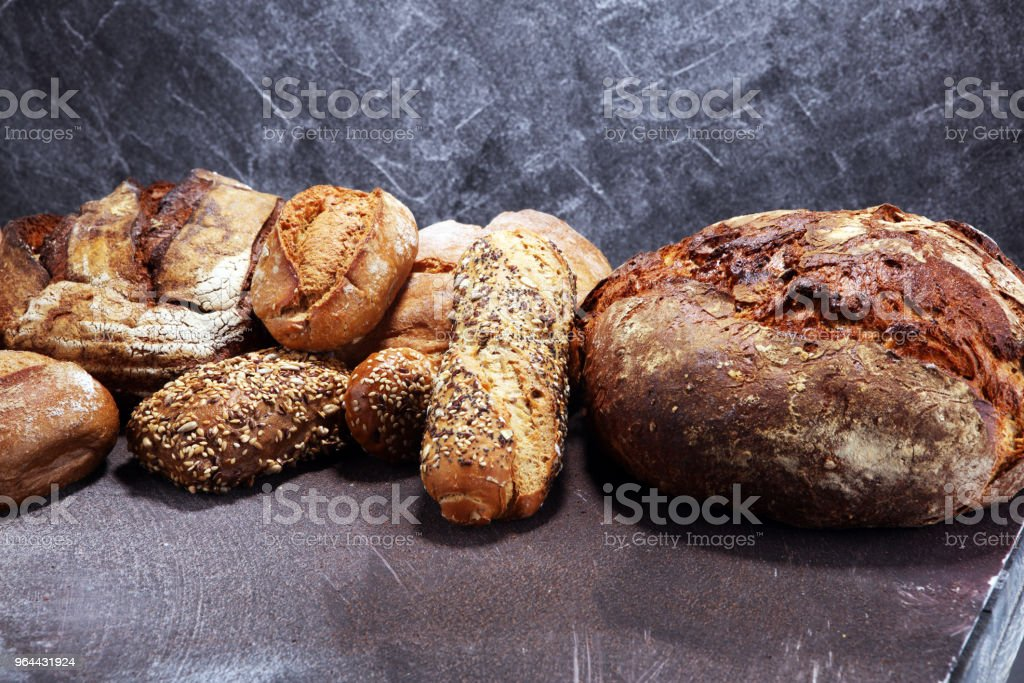 Different kinds of bread and bread rolls on board from above. Kitchen or bakery - Royalty-free Baguette Stock Photo