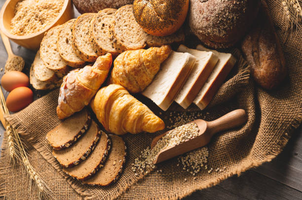 different kinds of bread with nutrition whole grains on wooden background. food and bakery in kitchen concept. delicious breakfast gouemet and meal. - crosta geologia foto e immagini stock