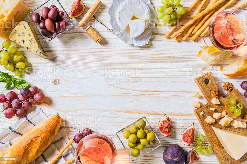 Different kinds of cheeses, wine, and snacks on the white - Photo