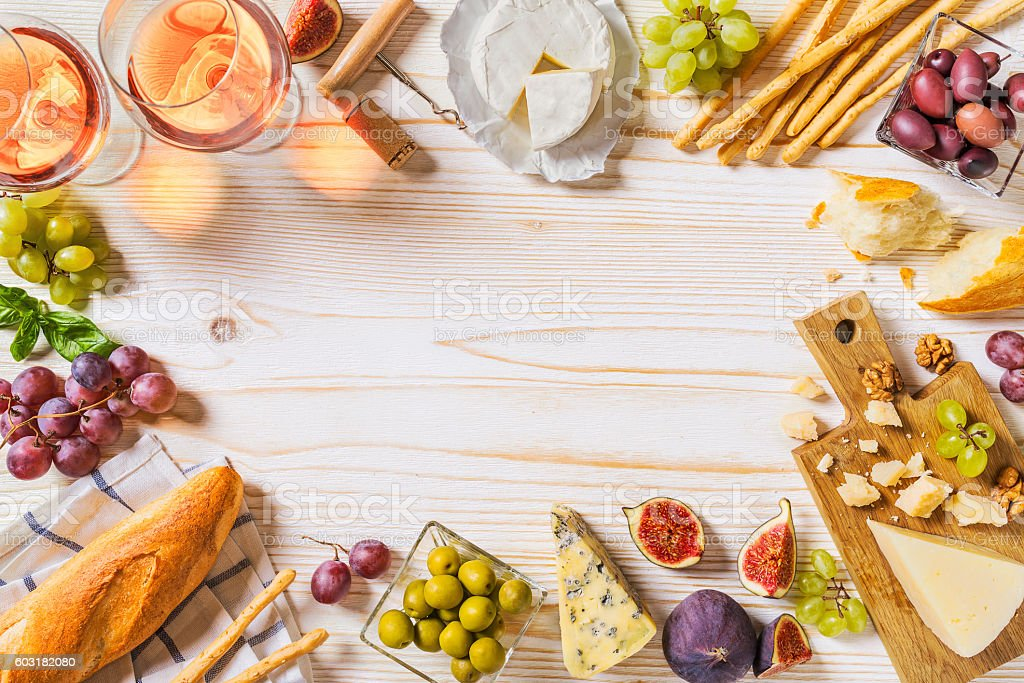 Different kinds of cheeses, wine, baguettes and fruits on white - Photo