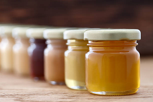 verschiedene arten von honig in einer reihe - kastanienhonig stock-fotos und bilder