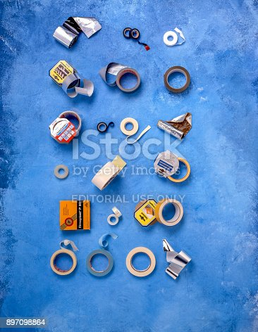 istock 20 different kinds of insulating and sticky tapes on a blue background 897098864