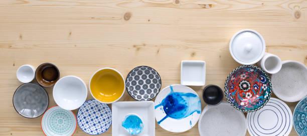 Verschiedene Arten von modernem, farbenfrohen und weißen Geschirr in verschiedenen Designs auf hellem Holzhintergrund – Foto
