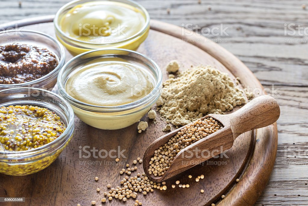 Different kinds of mustard on the wooden background stock photo