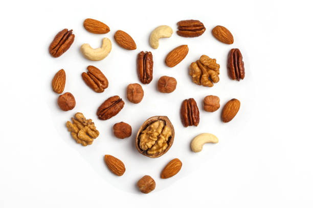 Different kinds of nuts laid out in the shape of a heart, isolated on white background. stock photo