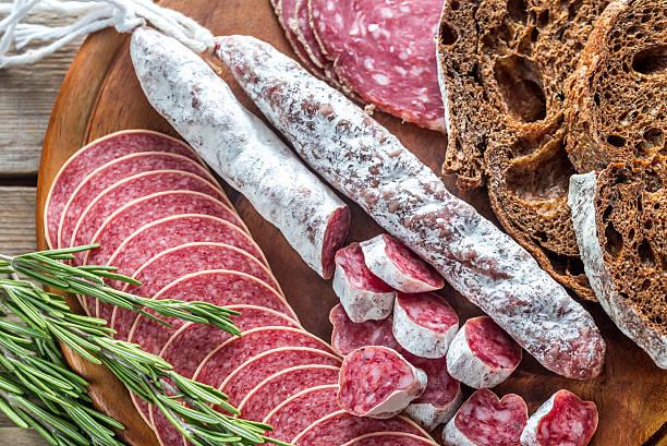 different kinds of salami with dark-rye bread - fuet sausages fotografías e imágenes de stock