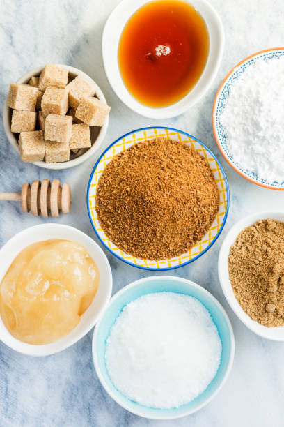 Different Kinds of Sugar and Sweeteners in the Bowls Different Kinds of Sugar and Sweeteners in the Bowls, such as coconut, pure cane, icing, maple syrup, dark brown soft sugar, honey, demerara cubes sugar cane stock pictures, royalty-free photos & images