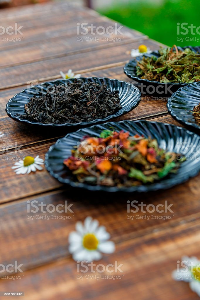 Different kinds of tea on black plates stock photo