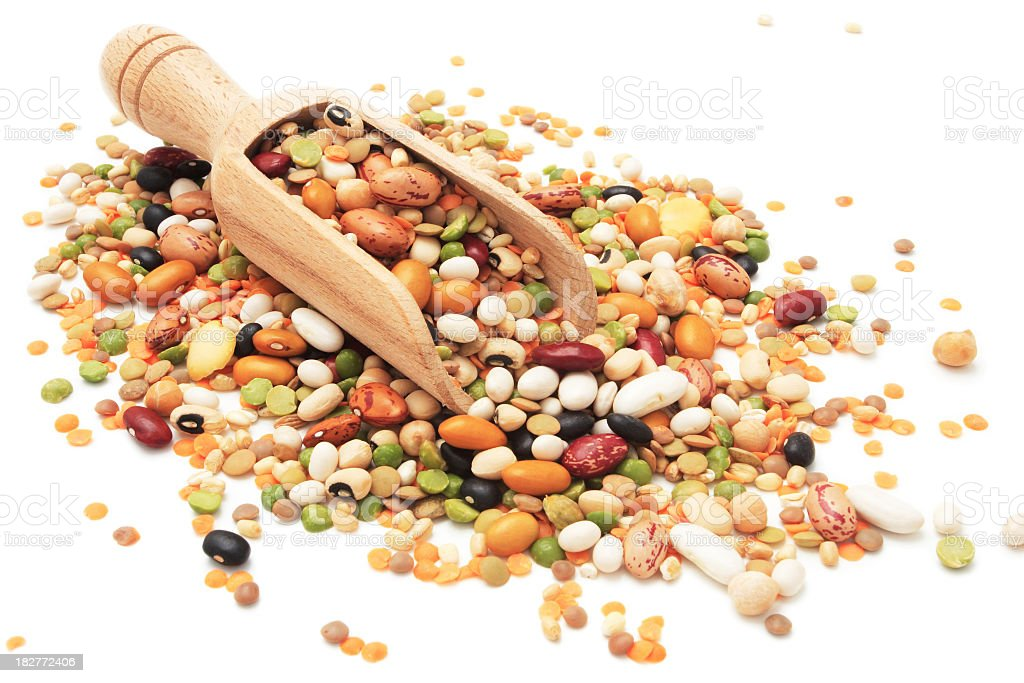 Different legumes and beans spilled around a wooden scoop stock photo