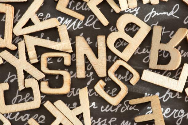 Different letters on a background with words Verschiedene Buchstaben auf einem Hintergrund mit Worten illiteracy stock pictures, royalty-free photos & images