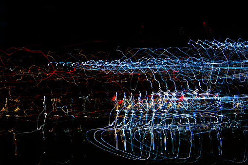 824108398 istock photo Different light trails of multicolored street lanterns and passing cars scattering in the dark 1149144838