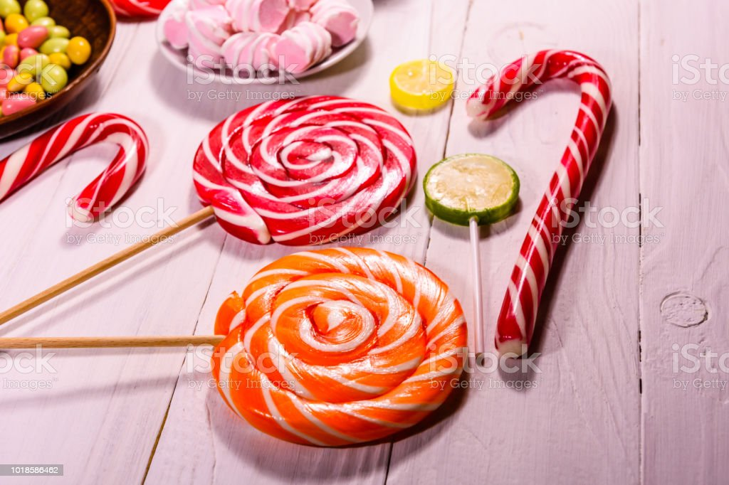 Different Lollipops On A White Wooden Table Stock Photo & More