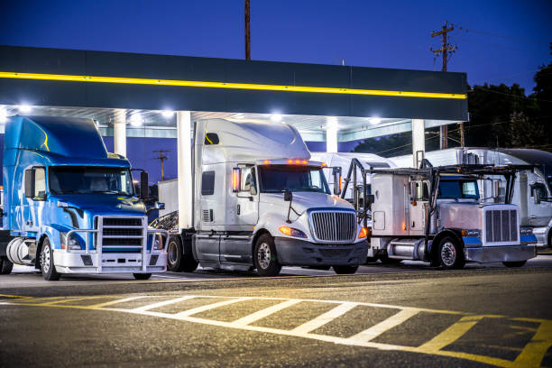 Different make and models big rig semi trucks with semi trailers standing on the truck stop parking lot under the lighted shelter in night stock photo