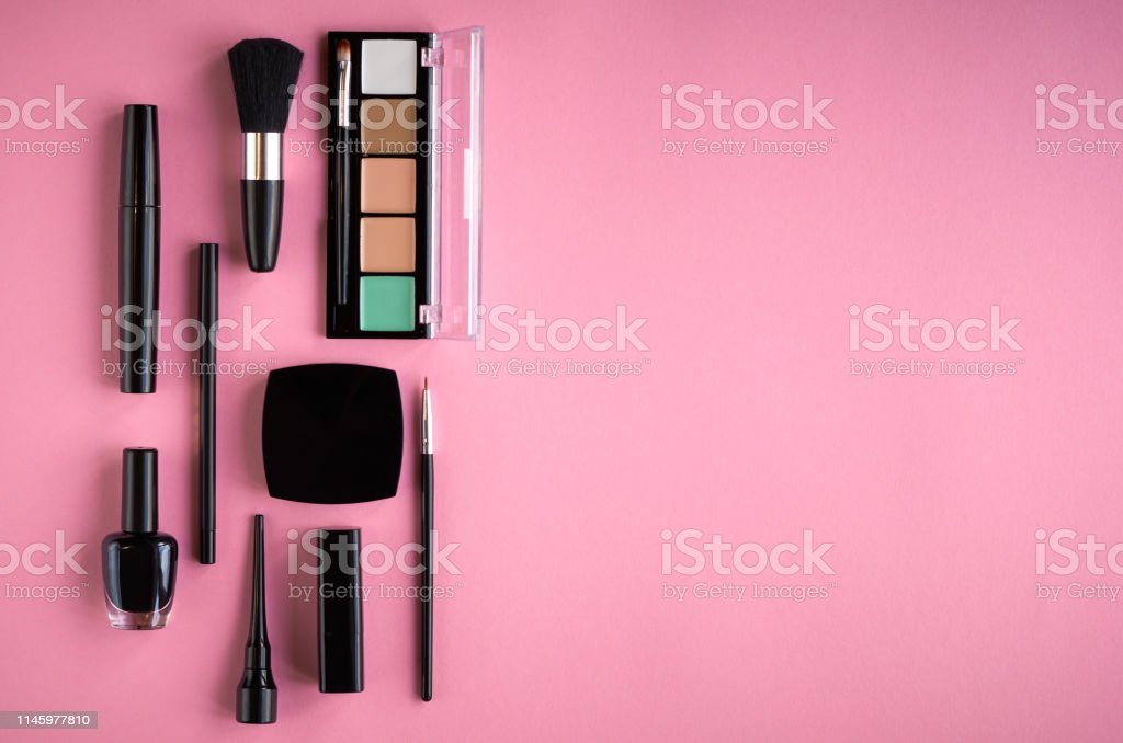 Different makeup products composition on pink background, flat lay...