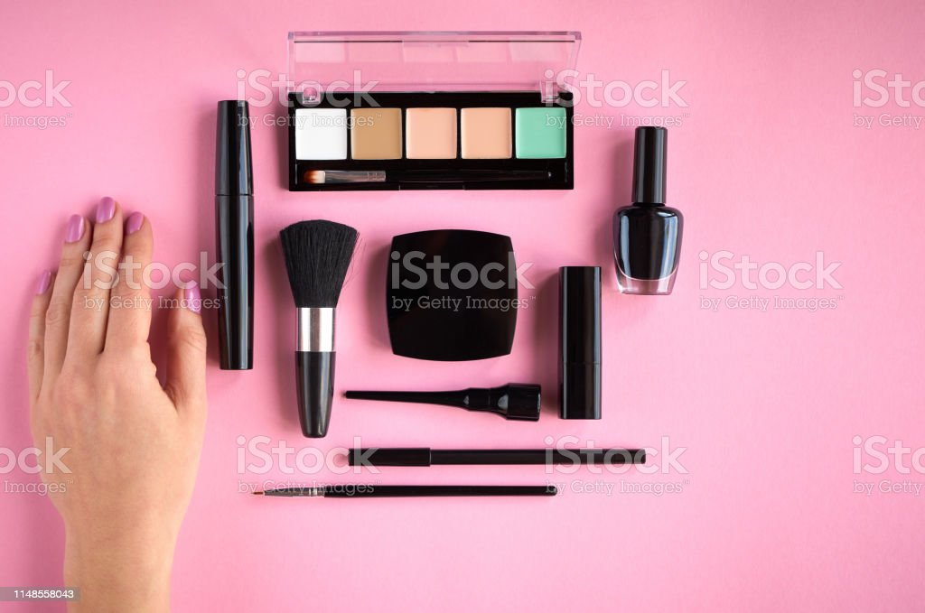 Different makeup products composition with hand on pink background,...