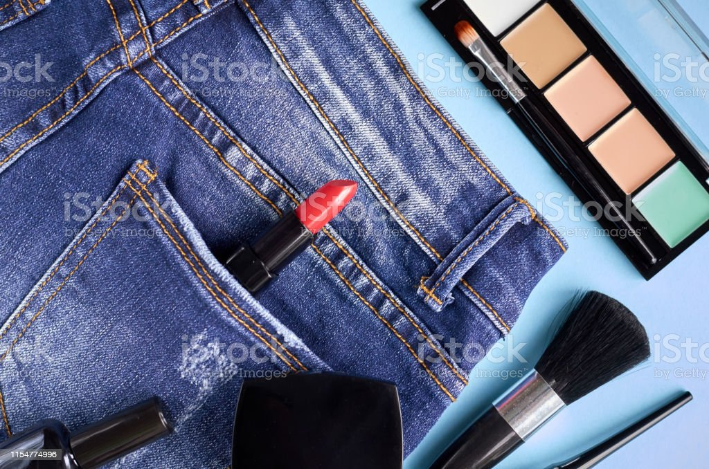 Different makeup products composition with jeans on blue background,...