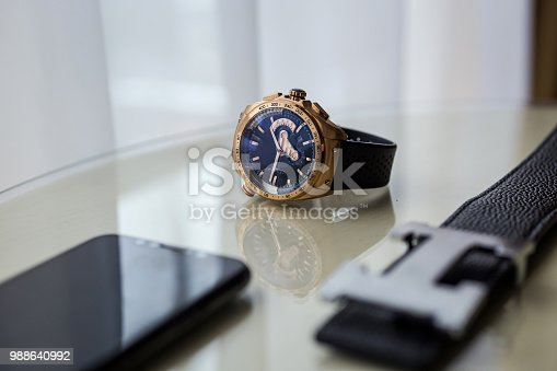 625840656 istock photo Different men's accessories such as: belt, watches and telephone - are on the table 988640992