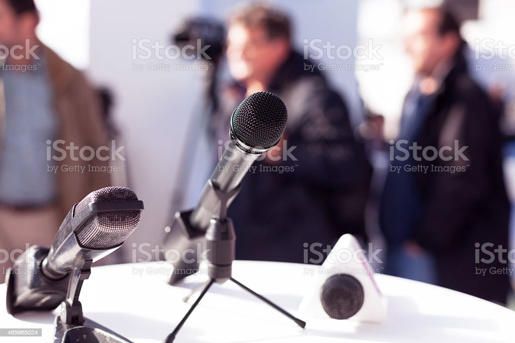 3 different microphones sitting on table at press conference stock photo