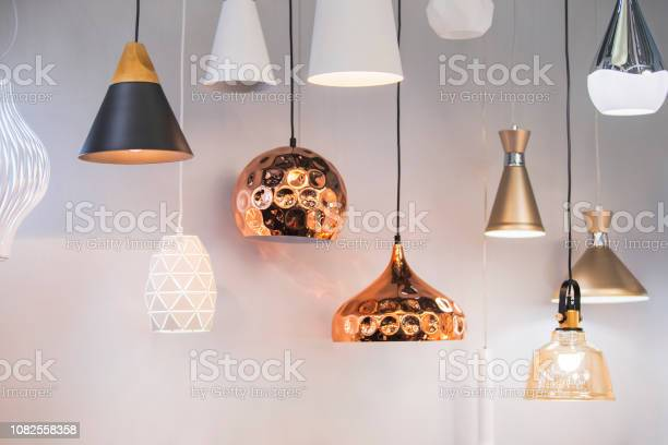 Photo of Different modern streamlined mirror copper chandeliers. Bubble metal copper shade pendant