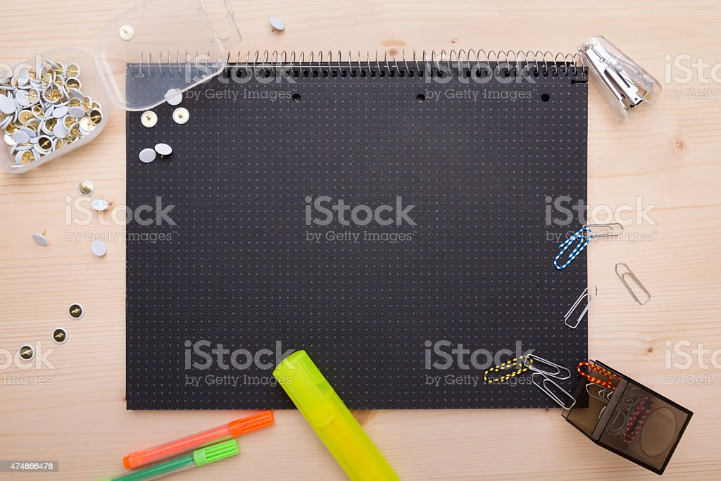 Different office objects arranged on a black piece of paper stock photo
