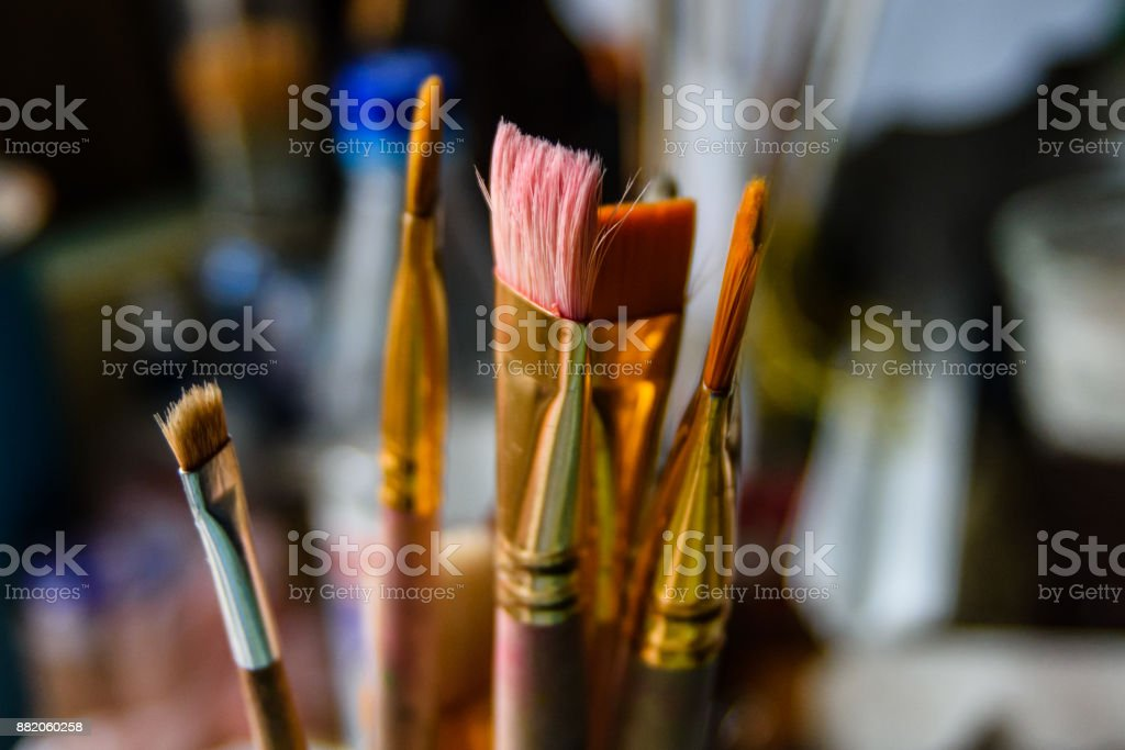 Different paint brushes in art studio stock photo