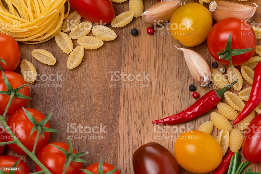different pasta, spices and cherry tomatoes on a wooden board stock photo