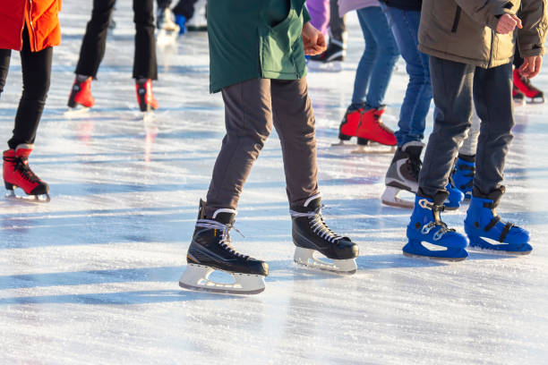 different people are actively skating on an ice rink. hobbies and leisure. winter sports stock photo