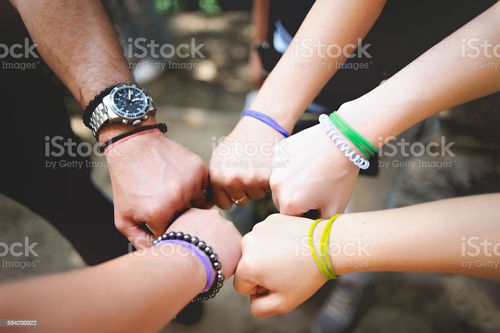 Different people put a hand in the center outdoor stock photo