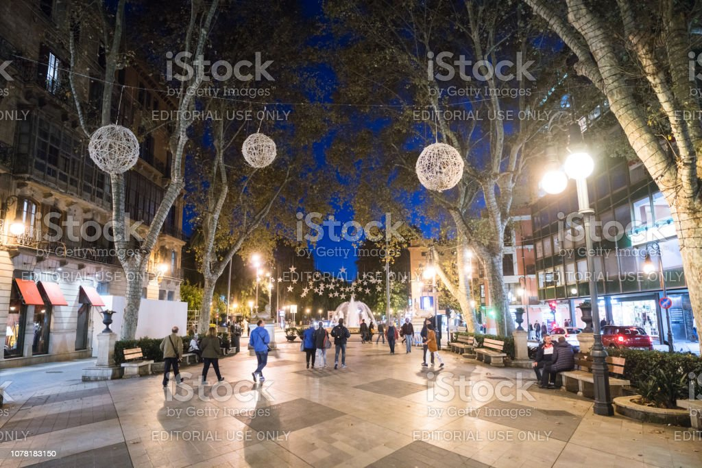 Different people walking on the Passeig des Born promenade of Palma in nighttime stock photo