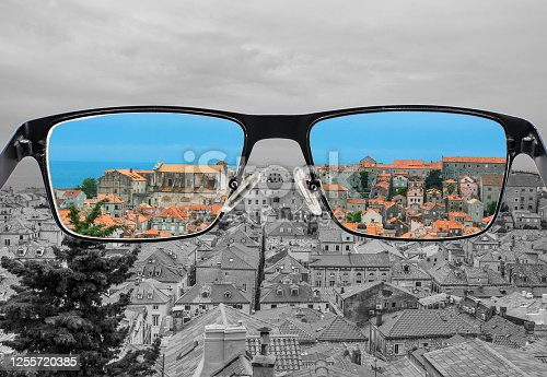 istock Different perception of world. Colorful view of red roods and blue sea in  Looking through glasses. 1255720385