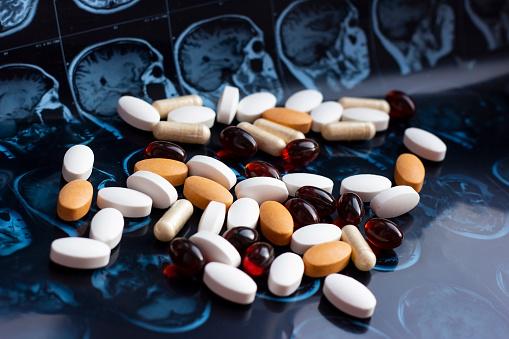 istock Different pharmaceutical medicine pills on magnetic brain resonance scan mri background. Pharmacy theme, health care, drug prescription for tumor, alzheimer, mental illness treatment medication 1141924079