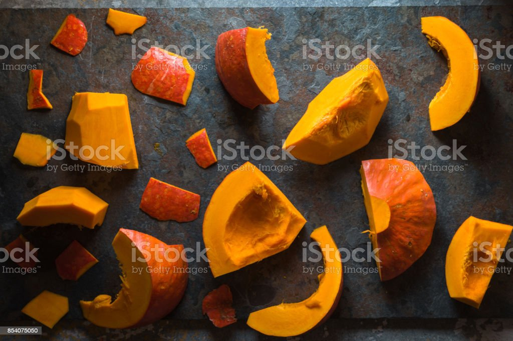 Different pieces of a pumpkin on a blue stone stock photo