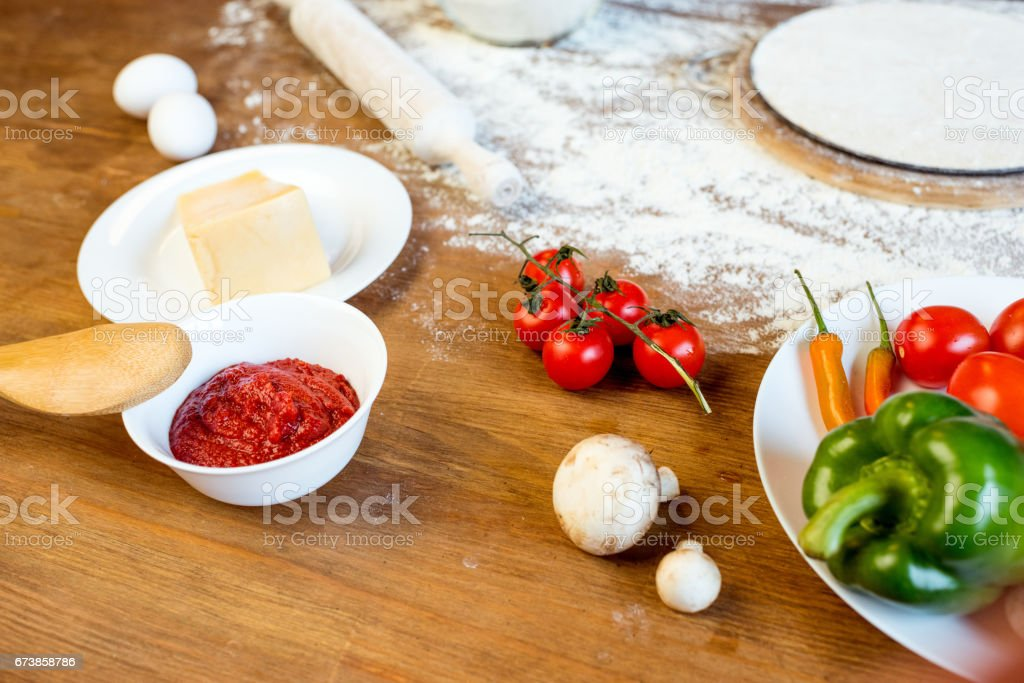 different pizza ingredients, vegetables and dough on wooden tabletop photo libre de droits