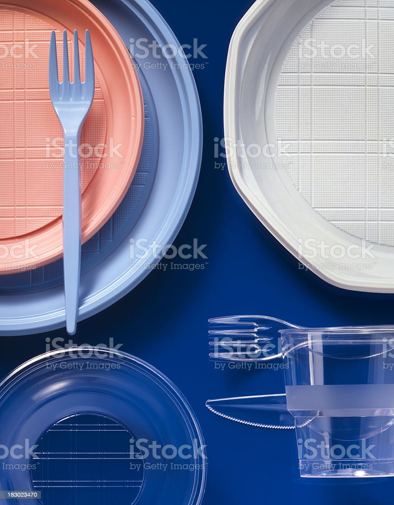 Different plastic cutlery and plates on blue background stock photo