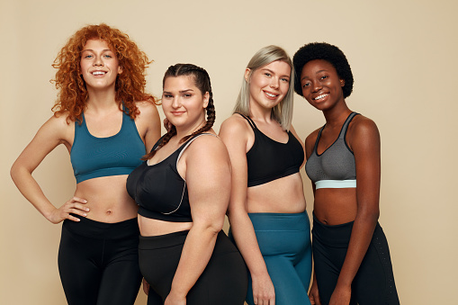 Different Race. Diversity Figure And Size Women Portrait. Smiling Multiethnic Female In Sportswear Posing On Beige Background. Body Positive As Lifestyle.
