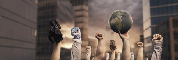 不同的上升左拳頭抗議氣候變化在城市前面和日落在景深 - 氣候 個照片及圖片檔
