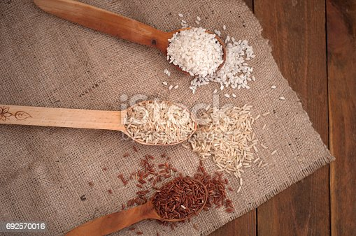 istock Different rice in wooden spoon: brown, red and round rice. The image is tinted 692570016