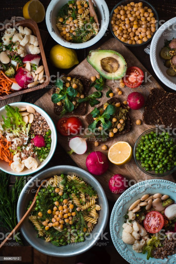 Different salad and appetizer on the wooden table top view stock photo