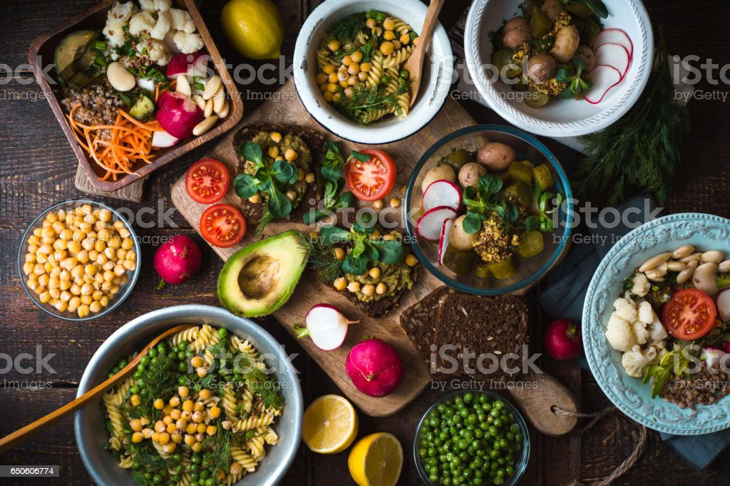 Different salad and snack on the wooden table top view stock photo