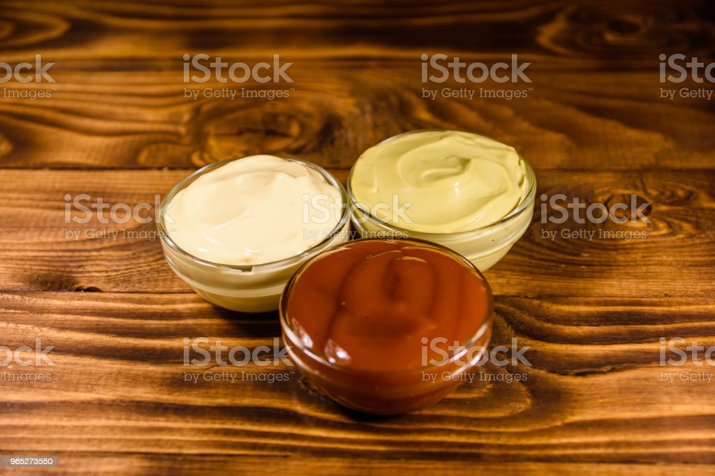 Different sauces in glass bowls on wooden table royalty-free stock photo