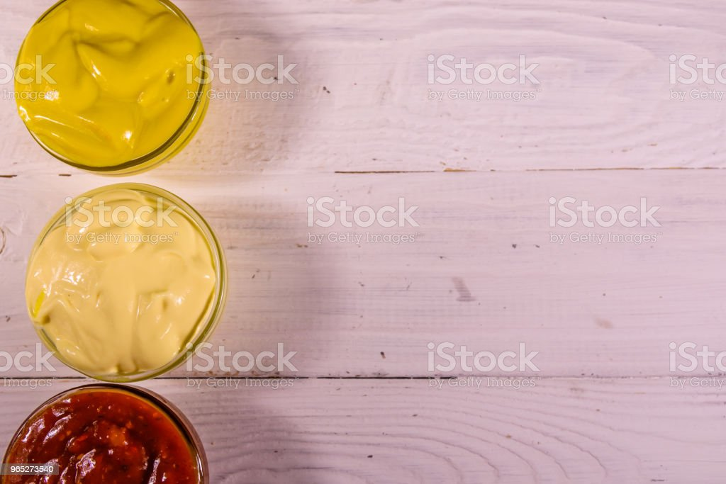 Different sauces in glass bowls on wooden table. Top view royalty-free stock photo