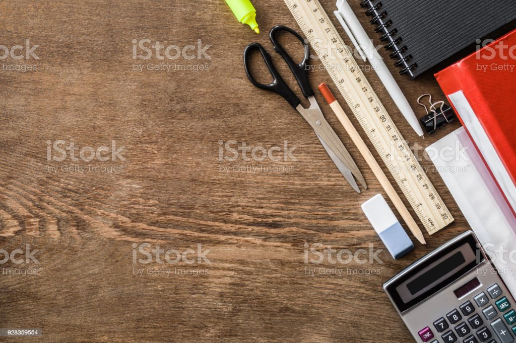 Different school or office supplies on a brown wooden desk. Education or business concept. Empty place for text. Flat lay. stock photo