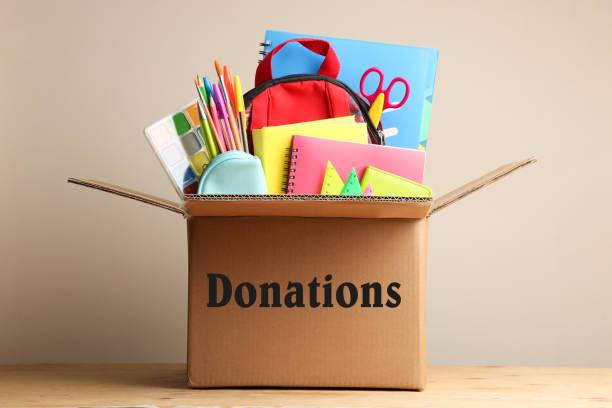 different school supplies in a cardboard box - cassetta per le offerte foto e immagini stock