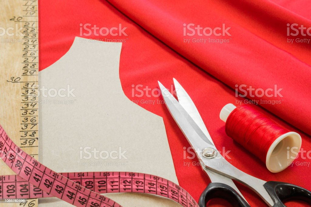 Different sewing items on bright red fabric. Handmade work. Closeup.