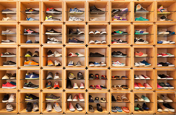 different shoes displayed in a shoe shop. - running shoes stockfoto's en -beelden