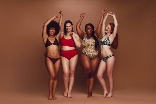 Different size women in bikinis dancing together Full length of different size women in bikinis dancing together over brown background. Multi-ethnic women in swimwear enjoying themselves. bikini stock pictures, royalty-free photos & images
